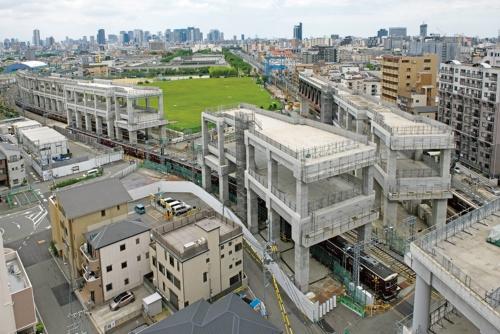阪急京都線(右)と千里線(左)が交差する淡路駅の南側から大阪都心方向を望む。高架の上層を大阪方面に向かう列車が、下層を京都方面に向かう列車が走る計画。遠くに大阪・梅田駅周辺の高層ビル群が見える(写真:生田 将人)