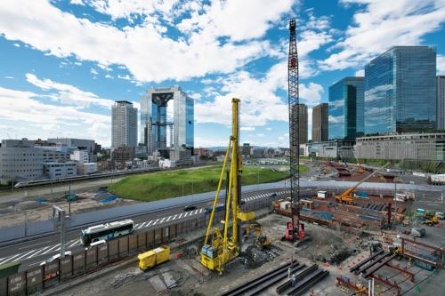 JR大阪駅北側にあった梅田貨物駅の跡地24haを開発する「うめきたプロジェクト」。敷地の南側から北側を望む。右手のビル群は、東寄りの7haを先行開発して2013年に完成したグランフロント大阪。現在は残り17haの2期区域の基盤整備が進む。写真左奥の地上を走るJR東海道線支線を移設、地下化して新駅を造る工事が最盛期を迎えている。中央左の超高層は1993年に完成した梅田スカイビル(写真:生田 将人)