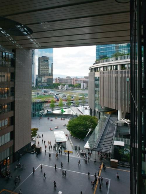JR大阪駅ビルの吹き抜けになったアトリウムから「うめきた」の敷地を見る。2024年夏ごろから順次完成する2期区域には、都市公園や植栽など甲子園球場2つ分に相当する計8haの緑地スペースを設ける。1万人規模のイベントが催せる広場も造る。右手はオフィスや商業施設、ホテルなどが入るグランフロント大阪(写真:生田 将人)
