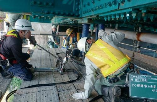 写真3■ 設計段階で垂直材の張力を測定する川田工業の技術者(写真:国土交通省)