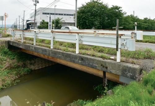 写真1■ 嵐北地区の橋の例。主桁が腐食し、床版は鉄筋が露出している(写真:日経コンストラクション)
