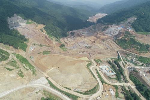 写真1■ 2019年8月時点の成瀬ダムの建設現場の様子。本体基礎掘削工事や法面保護工事などが進む(写真:鹿島)