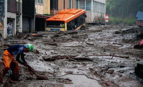 写真1■ 大量の土砂が市街地に流れ込み、住宅や車を巻き込んだ。7月3日撮影(写真:AFP/アフロ)