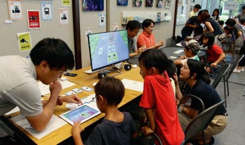 写真1■ ポケドボで遊ぶ子どもたち。手前はアプリ版のポケドボで、災害カードを引くと派手なアニメーションが流れる(写真:光安 皓)