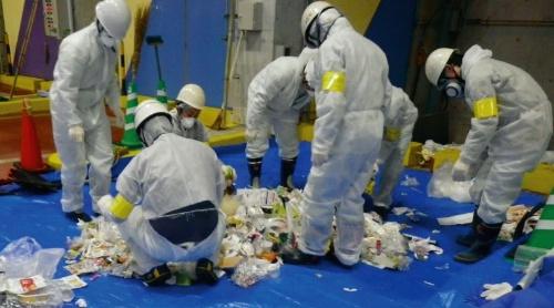 写真1■ ごみの組成調査の様子。処理施設に集められたごみ袋を開け、中身を紙類やプラスチックなど30種類以上に分類する(写真:八千代エンジニヤリング)