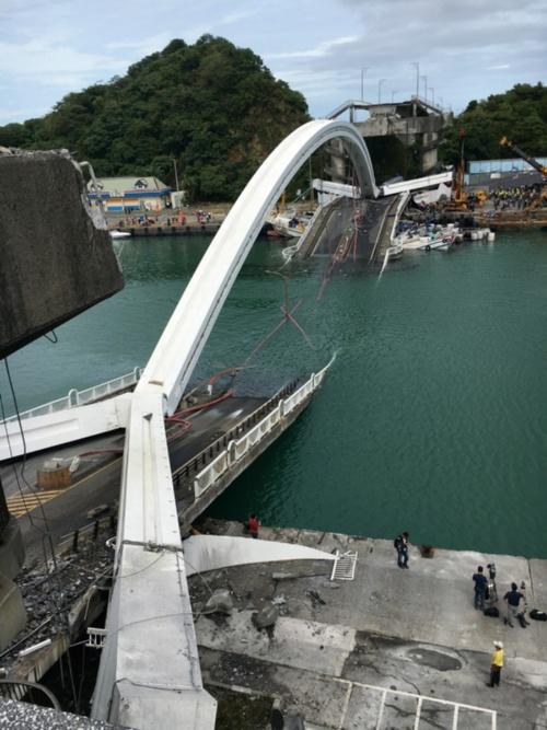 写真1■ 落橋した南方澳跨港大橋。奥が港側。赤く見えるのはケーブルのシース。橋長140m、幅15mで完成から21年が経過していた。建設費は2億7000万台湾元(約9億4000万円)。事故後、台湾の蔡英文総統は全土の老朽橋を早急に点検するよう指示した(写真:王 仲宇)