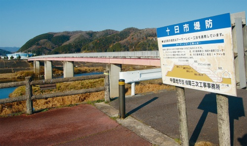 写真1■ 馬洗川では、アーマーレビー工法によって堤防を強化した旨を、簡易な図面とともに現場に掲げている(写真:日経コンストラクション)