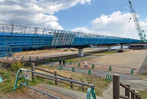 写真2■ 右岸側の宮城県登米市から見た豊里大橋。手前の下流側は新しい鋼床版鈑桁に架け替え済み。20年3月に撮影(写真:日経コンストラクション)