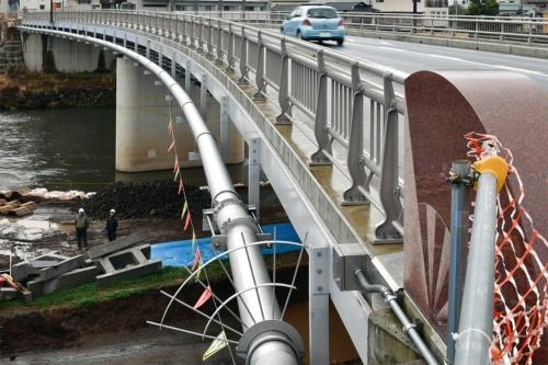 写真1■ 熊本市内の白川に架かる明午橋。2018年10月に完成した橋長103mの鋼2径間連続鋼床版箱桁橋だ。橋桁の下流側に市が配水管を添架した。補修後の20年3月に撮影(写真:日経コンストラクション)