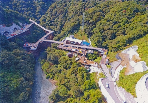 写真1■ 中津川橋の施工現場。中央を中津川が流れる。主塔や橋脚の深礎を掘削する工事などが進んでいる(写真:中日本高速道路会社)