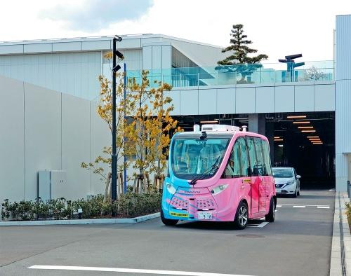 写真1■ 羽田空港に近い羽田イノベーションシティ内を循環する自律走行バス。一般車両も立ち入る道路を走る。全地球測位システム(GPS)や3次元レーザースキャナーなどで障害物を避けながら設定したルートを走行。鹿島は空間情報データ連携基盤「3D K-Field」を提供した(写真:日経コンストラクション)