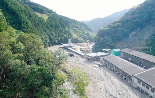 写真1■ 熊本県球磨村の松野地区における土砂・洪水氾濫の被災状況。建物のすぐ横を流れていた川は、大量の土砂で埋まっている。写真手前が上流側(写真:砂防・地すべり技術センター)