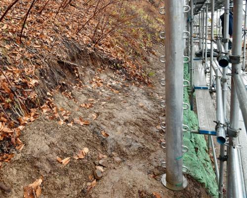 写真2■ 事故後の20年11月に撮影した現場。落石防護柵の支柱の位置を道道北見常呂線寄り(写真右の方向)に1.1mずらして供用中の水道管を避けた(写真:日経コンストラクション)