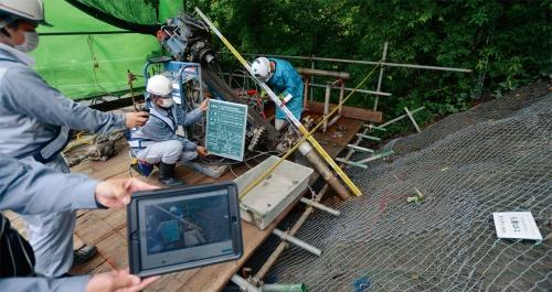 写真1■ 西日本高速道路会社が発注した松山自動車道法面補強工事で奥村組土木興業が遠隔臨場に対応している様子。この現場では新型コロナウイルスの感染拡大よりも前から奥村組土木興業の提案で試行を始めていた。2020年6月に撮影(写真:日経コンストラクション)