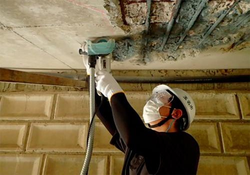 写真2■ 掃除機に接続した改良工具で、床版の裏をはつっている様子(写真:玉名市)