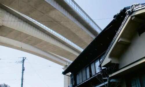 写真1■ 被害を受けた住民宅付近から見上げた新東名高速道路の橋桁(写真:住民側弁護団)