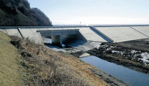 写真1■ 完成時の防潮堤。上部には県道が通る。ボックスカルバートを組み込んで河川を通す複合的な構造だ(写真:岩手県)