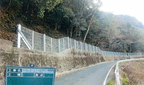 写真1■ 完成時の落石防護柵。斜面が防護柵に迫り、平場はほとんどないように見える(写真:宮崎県)