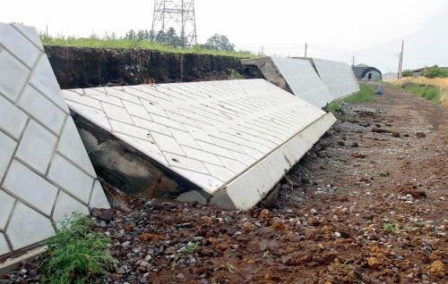 写真1■ 降雨の影響で2015年6月、群馬県渋川市にある北橘運動場の擁壁の一部が倒壊。背後の盛り土の表面や前面の道路は未舗装だった(写真:朝日新聞社)