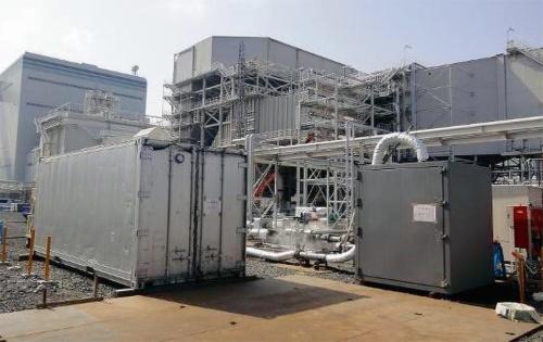 写真2■ 島根県浜田市にある三隅発電所にコンテナ養生槽を設置した(写真左)。養生槽内にはコンクリートを置き、発電所から出る排ガスを養生槽に入れる(写真:鹿島)