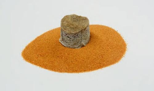 写真1■ 下に敷いている砂漠の砂から製造した硬化体。砂はナミビアのナミブ砂漠から取ってきた(写真:日経コンストラクション)