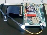 NTTの分散深層学習向けアクセラレーター。ボードの奥左側の送受信モジュール2つは、100Gビット/秒の光リンク。黒い台に見えるのはサーバーの筐体(写真:NTT)