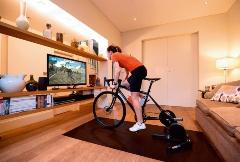 (a)自転車の後輪側に負荷発生装置を取り付けてズイフトのサイクリングアプリをプレイする様子