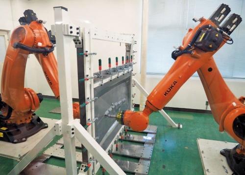 図1 対向式ダイレス成形技術でボディーパネルを成形するロボット