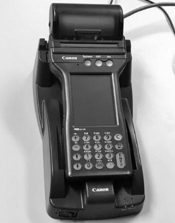 通信用アダプターに載せたハンディターミナル。通信用アダプターにIPアドレスを割り当てていて、LANに接続して通信できる