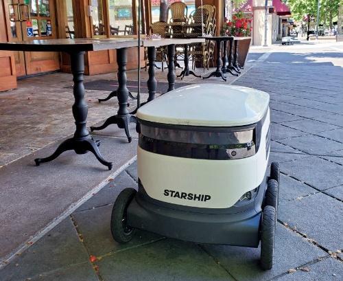 (a)レストランの前に停車中の配送ロボット