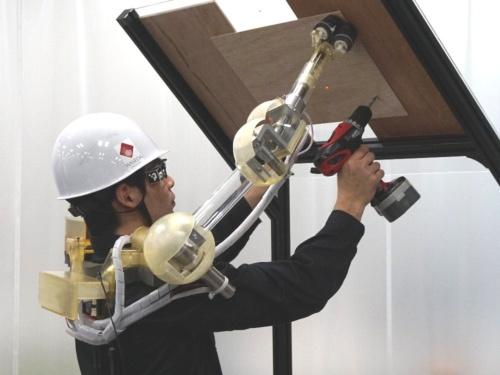 ベニヤ板をロボットアームで支えてビス止め作業を支援する様子