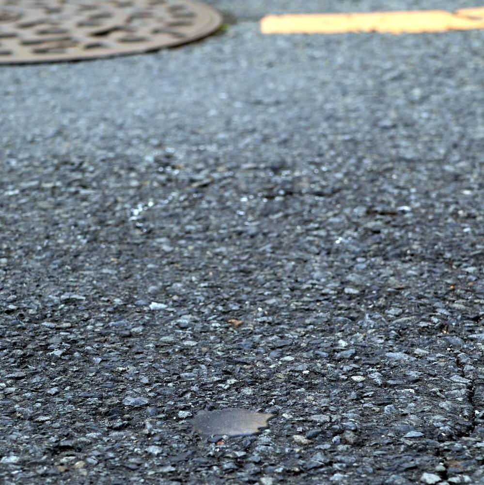 路面の黒い補修材の下に磁気マーカーがあり、運転制御に使う