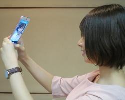 歯周病の判定をするためにスマートフォンで歯ぐきの撮影をしている様子