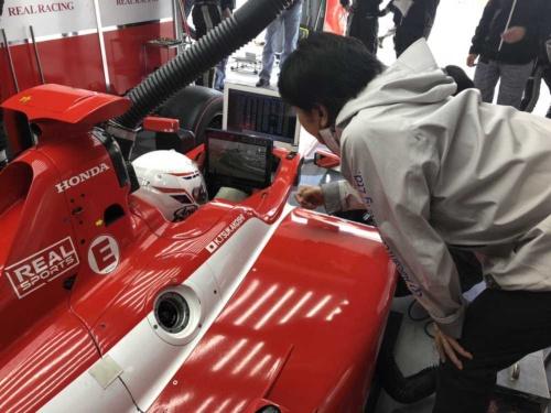 2018年の「全日本スーパーフォーミュラ選手権」のピットで、アビームコンサルティングのスタッフがドライバーの塚越広大選手にデータ解析結果を伝える様子。走行中は音声で伝える必要がある