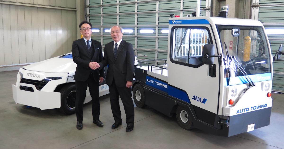 豊田自動織機の一条恒常務役員(左)とANAの清水信三専務執行役員。後方左が完全自動運転できる燃料電池駆動の牽引車のコンセプトカー、後方右が今回の実証実験用の電動牽引車