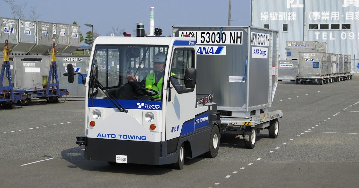 佐賀空港内のコースでコンテナを牽引しながら走行する電動牽引車。運転席の従業員は万一に備えブレーキペダルに足を掛けているものの、加減速やハンドル操作などの運転操作をしない