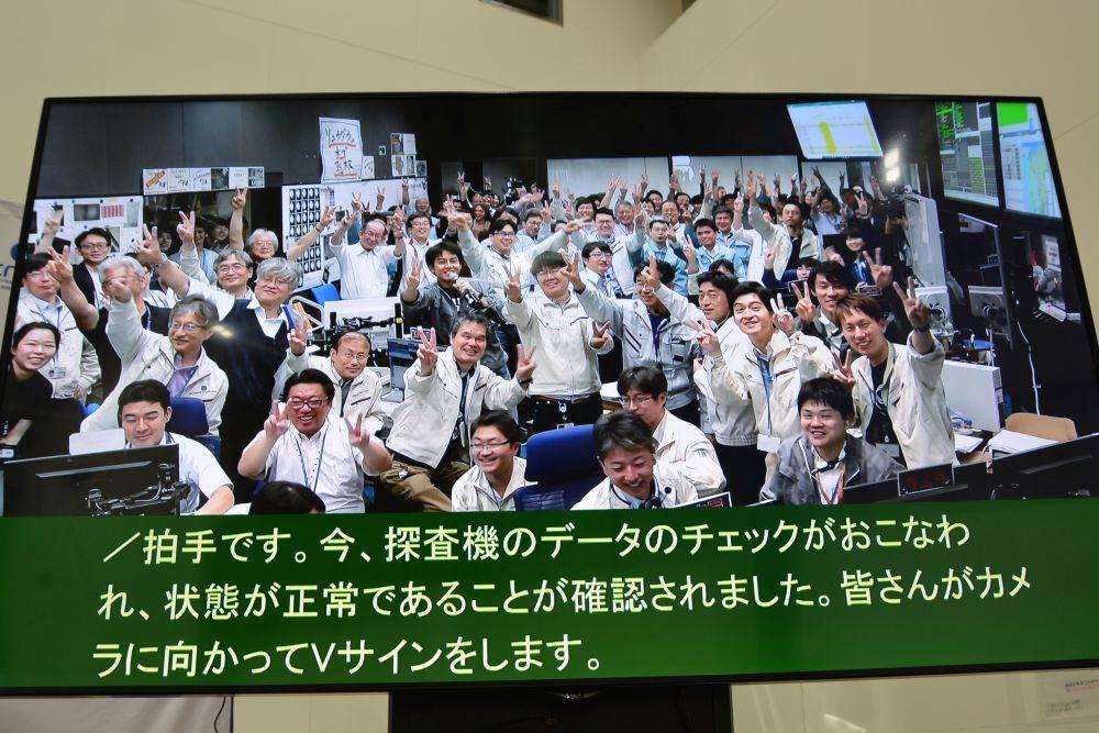 図2 2回目のタッチダウン成功でVサインで喜びを示す管制室のメンバーら (撮影:日経 xTECH)