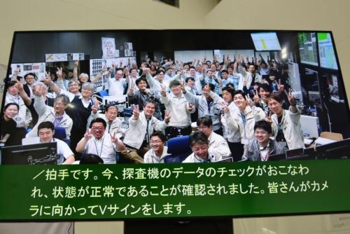 図2 2回目のタッチダウン成功でVサインで喜びを示す管制室のメンバーら