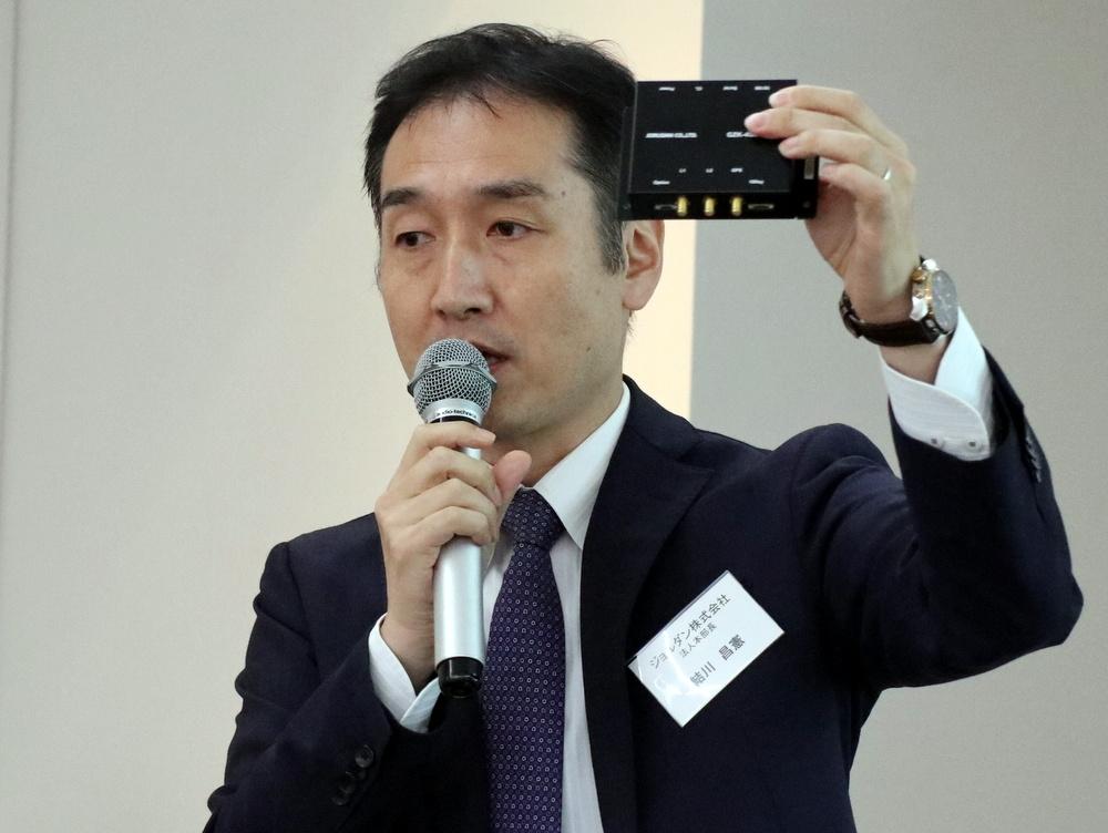 バスロケーションシステム用の車載器を掲げるジョルダンの結川昌憲執行役員