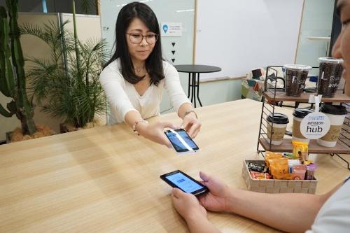 Amazon Hubカウンターのイメージ。店舗スタッフはスマホアプリで利用者のバーコードを読み取る