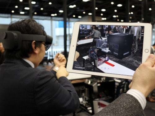 HoloLens 2を使ったデモ。タブレット画面に表示されているのがHoloLens 2を装着したオペレーターの視界に見える映像。記者会見場にデロンギのコーヒーマシンが浮かび上がっている