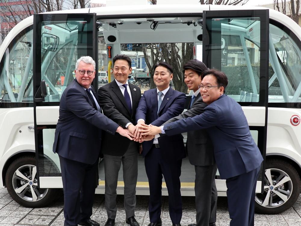 自動運転バス「ARMA(アルマ)」の前で記念撮影に望む茨城県境町の橋本正裕町長(中央)ら