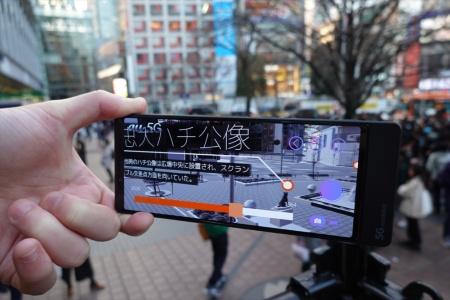 渋谷のスクランブル交差点方面の1964年当時の再現画像が、5G対応のスマートフォンに表示された様子