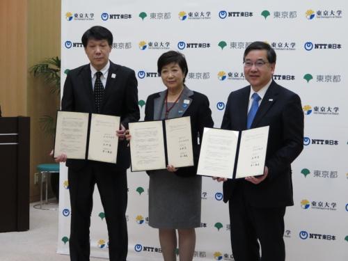 連携協定の締結式に登壇したNTT東日本の井上福造社長(左)、東京都の小池百合子知事(中央)、東京大学の五神真総長(右)