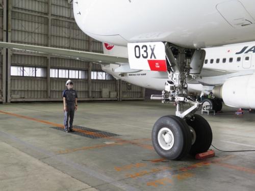 HoloLens 2を装着した整備士が航空機に近づいていく。リアルの工場見学では、見学者が機体の下に入ることはできない