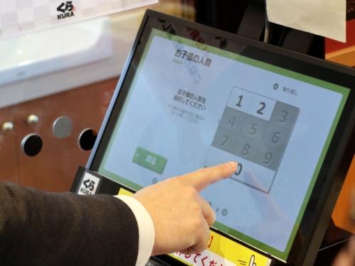 くら寿司東村山店の入り口にあるセルフ案内機。指を画面にタッチせずに近づけるだけで操作ができる