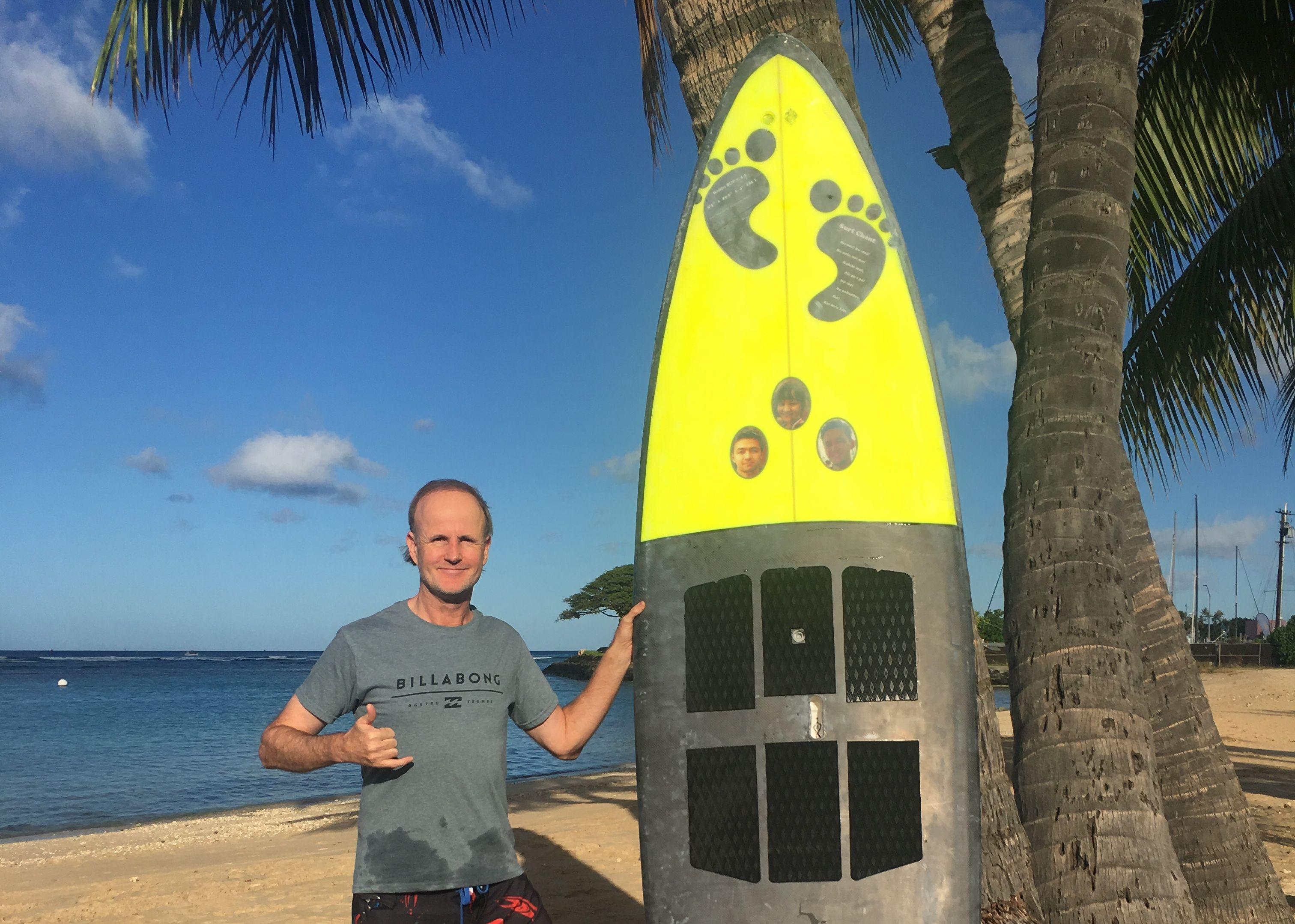 ハワイでサーフィンを楽しむミラー氏。ボードの自作にも取り組んでおり、このボードには3人の子供の写真をデザインしている (写真:クリフ・ミラー氏提供)