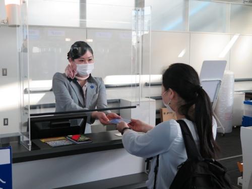 羽田空港で実施した実証実験の様子。コモンパスのデジタル証明書の画面を表示し、チェックインカウンターで係員に示す