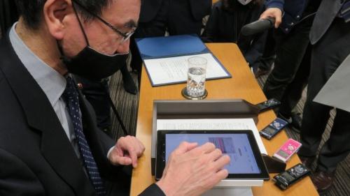河野太郎規制改革相がプラスチック製の台に置いたタブレット端末で接種券の「OCRライン」などを読み取る様子