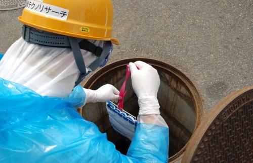 下水試料を採取する「サンプラー」をマンホール内に設置する様子
